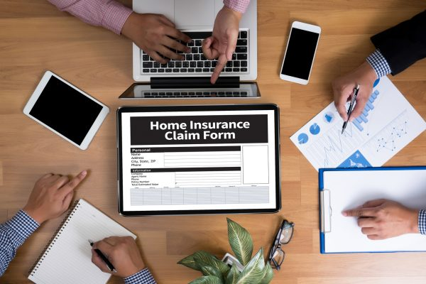 Home Insurance Claim Form Document Refund Home Insurance Business team hands at work with financial reports and a laptop, top view