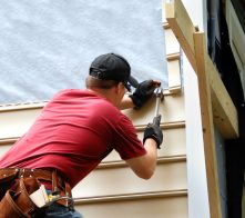 Young homeowner installs siding to his home.  He is holding a hammer and wearing a tool belt.